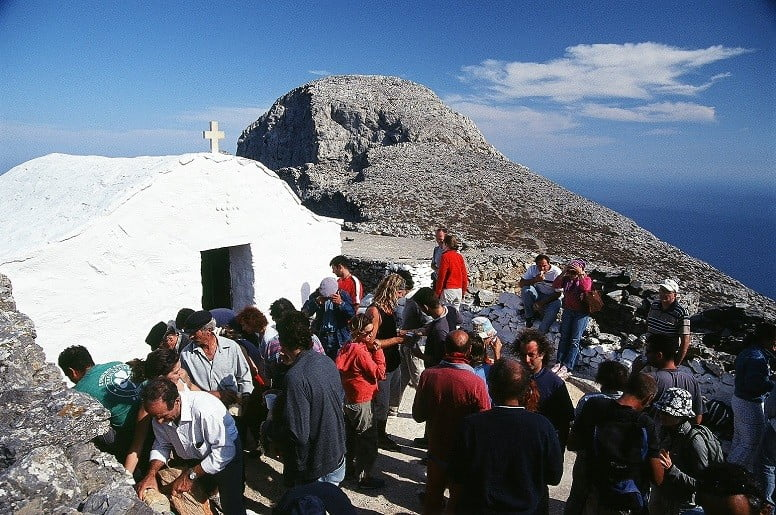 people front the church of Stavros (Holy Cross) commemorate Festival at Amorgos, Krikello, Greece and mountain in the background