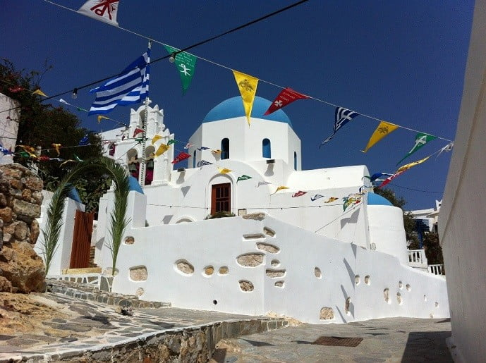 the church of Stavrou ('of the Cross') with blue cupola commemorate Festival at Donousa, Greece and mountain in the background