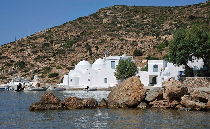 Church commemorate the Taxiarchis Festival at Sifnos, Vathi, Greece with mountain in the background and the sea in front