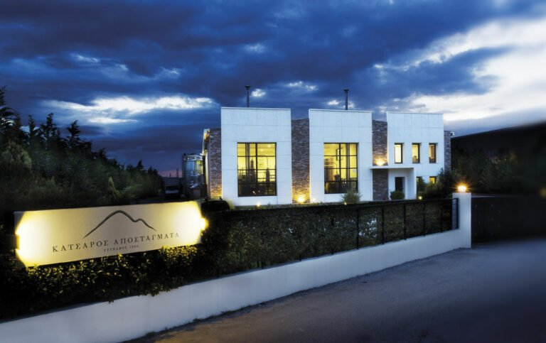 illuminated 'Katsaros Distillery' building by night with plants fence in the front